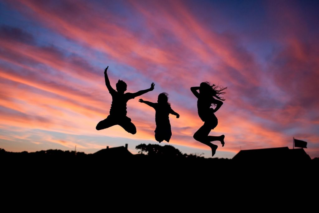 3 people jumping for joy at sunrise
